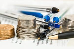 Stack of coins with pens and financial papers.