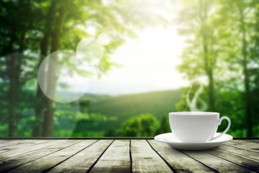 steaming cup of coffee on table with trees in background
