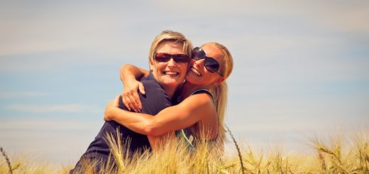 Mother and daughter hugging in a grain field
