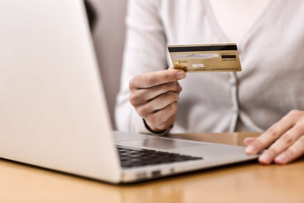 Woman holding a credit card with open laptop