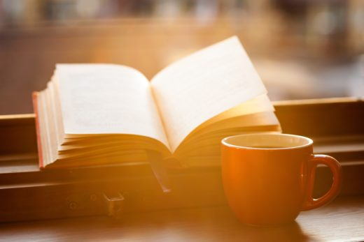 cup of coffee on table with book