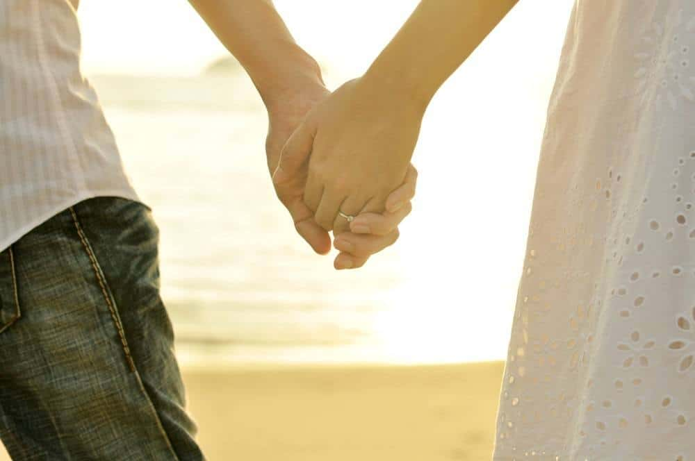 finances in marriage - married couple holding hands at sunset on the beach
