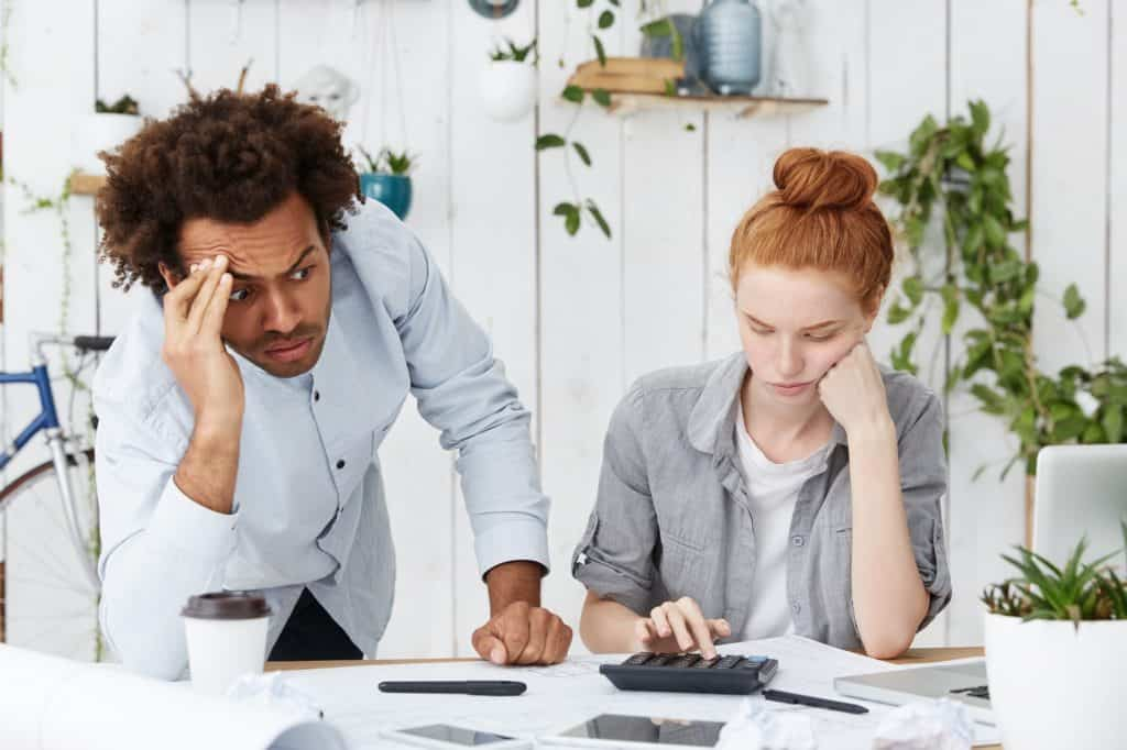 couple at desk looking stressed over bills