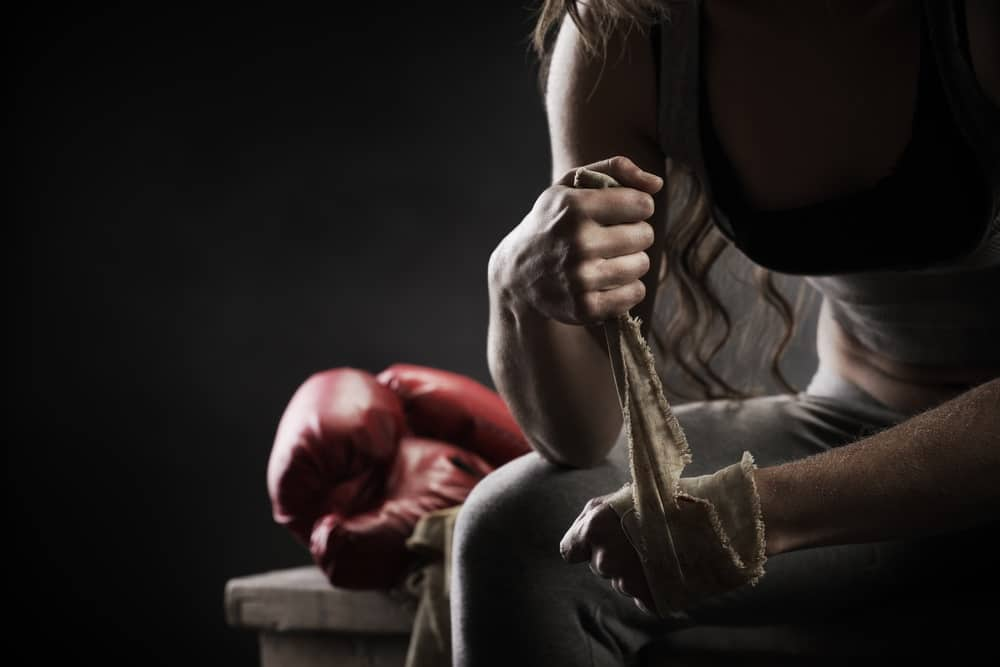 Female boxer on a bench wrapping hand with cloth, red boxing glove beside her