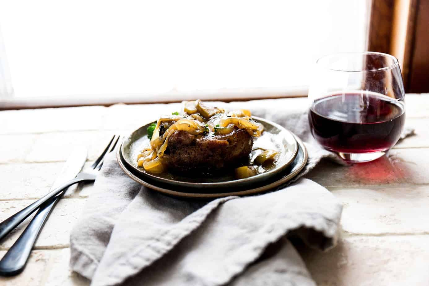 beef dish on a nice plate with red wine and cloth napkin