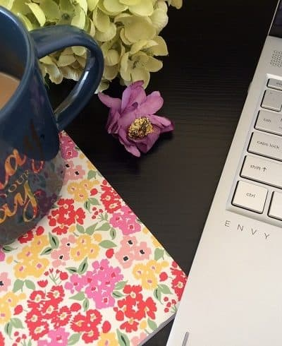 laptop, floral notebook, blue coffee cup on black desk: quiet place to increase work productivity
