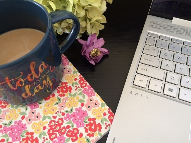 laptop, floral notebook, blue coffee cup on black desk: good work space for working productively