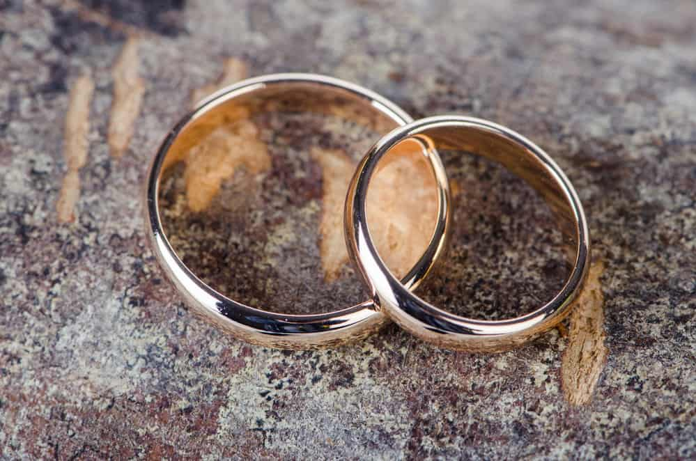 Two gold wedding rings on neutral granite countertop
