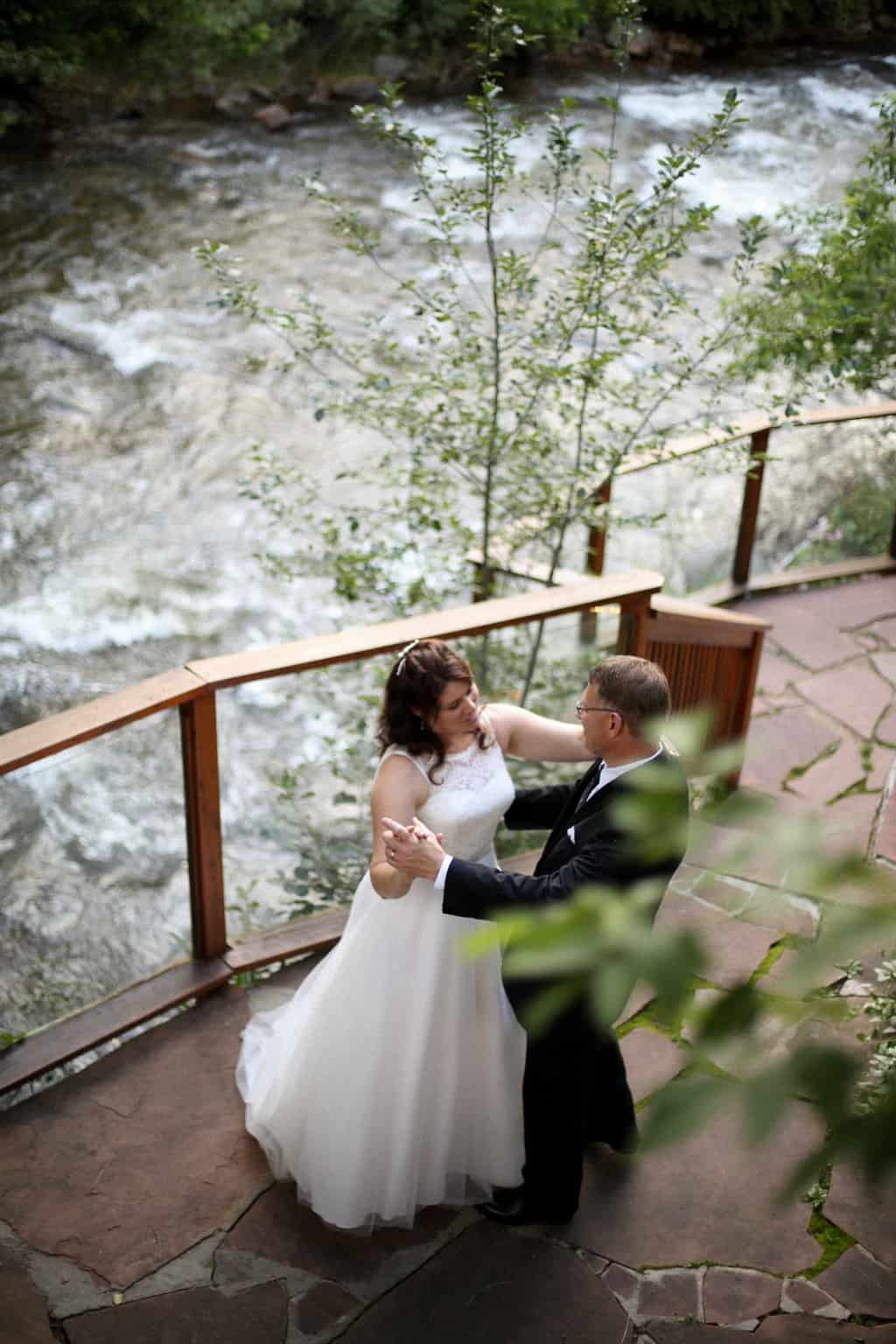 wedding couple dancing on red stone walkway by a rushing river