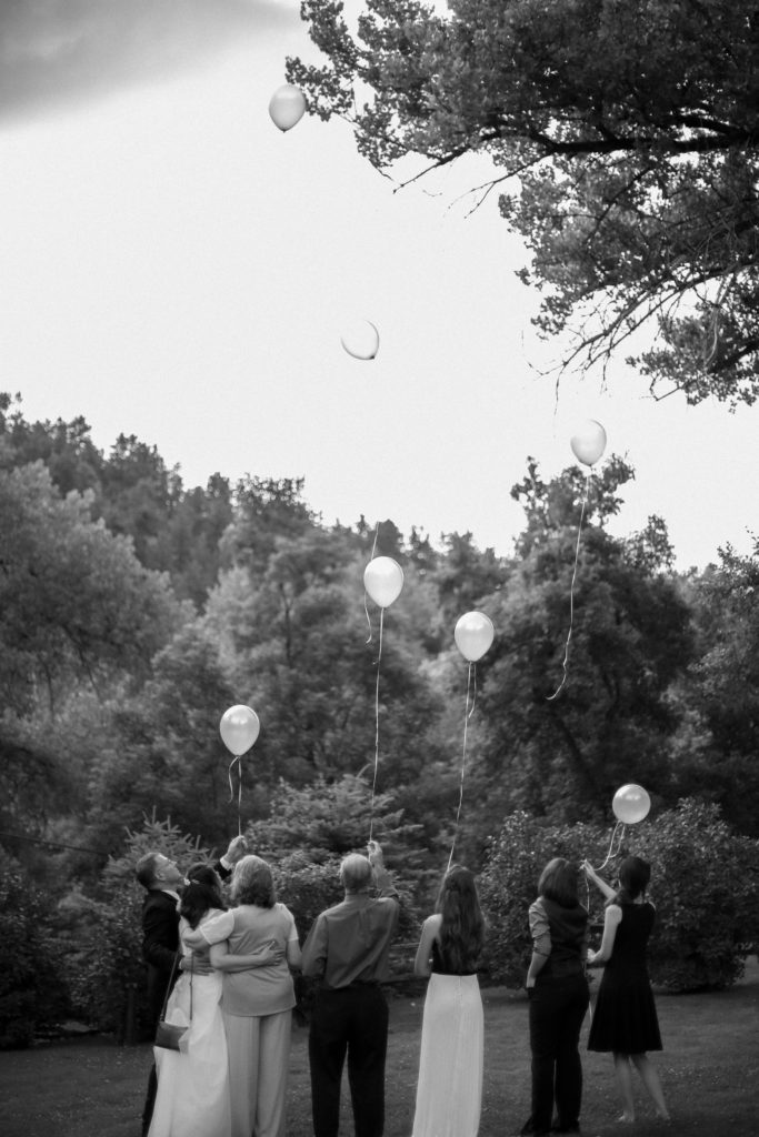 Wedding party on the lawn releasing balloons near trees