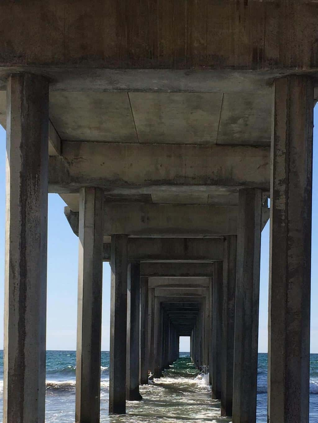 under the pier in La Jolla shot of rows of concrete leading into the water
