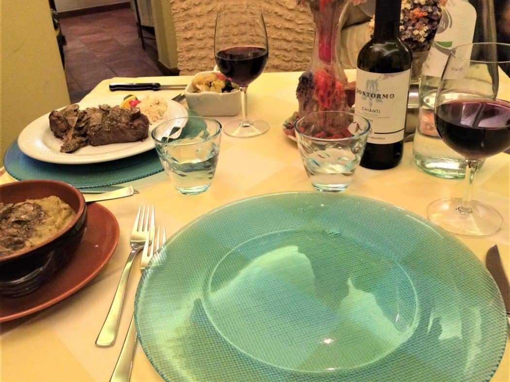 Dinner at a restaurant in Cortona, Italy - green glass plate, red wine bottle, steak and mushroom polenta