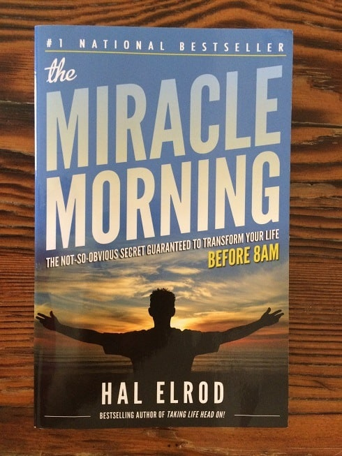 "image of book ""The Miracle Morning"" by Hal Elrod on wood table; how to set daily routines"