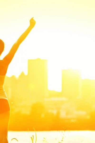 Woman with back turned in running shorts facing the sunrise with arms raised