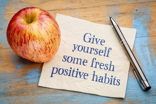 "apple and a note on a table that says ""give yourself some fresh positive habits"