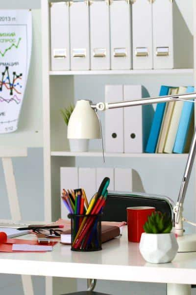 white desk in home office with colorful wall chart and bookshelves in background