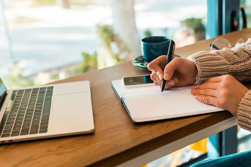 make a daily routine and stick to it- woman writing in notebook with open laptop in coffee shop