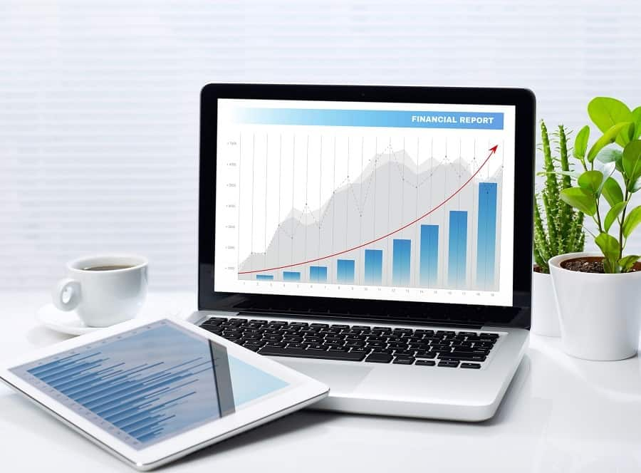 white laptop on white table with white tablet showing investment graphics