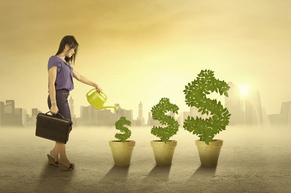 woman watering three pots with bushes in shape of money symbol