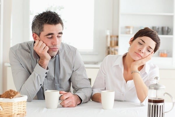 Tired couple in kitchen with coffee cups - snoring treatment may help