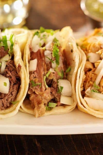 shredded beef tacos on a white plate