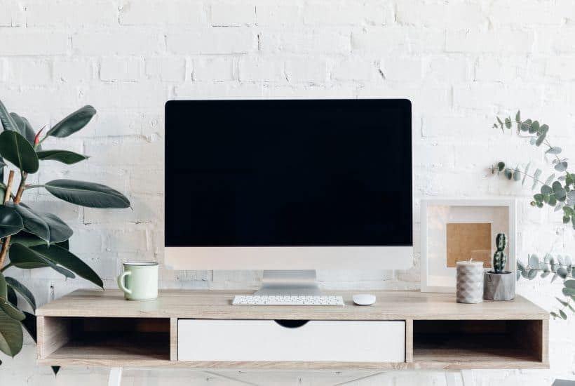 white desk with computer monitor in front of white brick wall