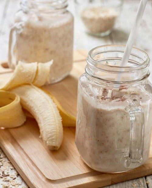 smoothie in ball jar with straw and banana on cutting board - healthy easy breakfast smoothies