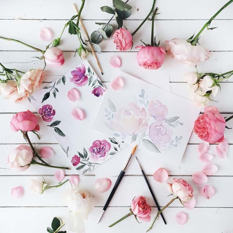 scattered flowers in a circle with varied colors of pink on a white table