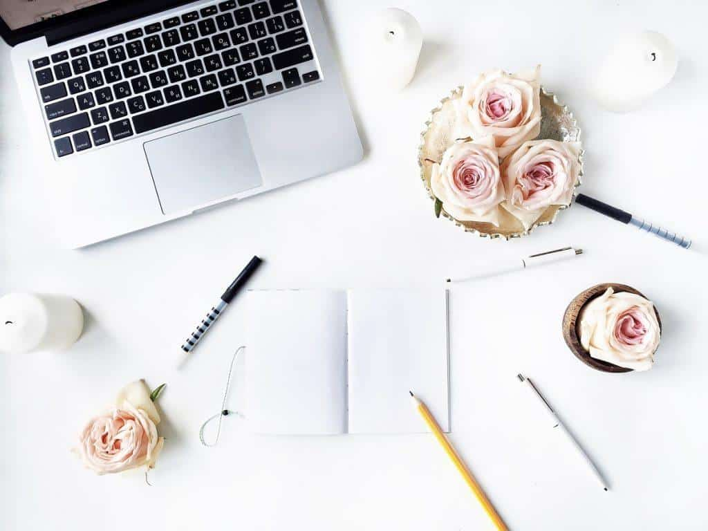 White desk with laptop and pale pink flowers --Seven Failproof Ways to Find Blog Post Ideas
