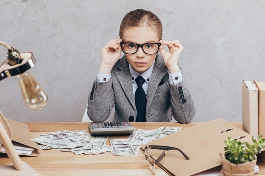 compound interest examples - child dressed in business suit with glasses at desk with money and calculator