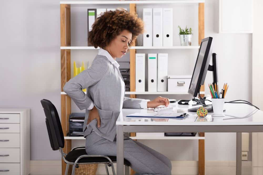 woman at a desk with back pain- adjustable height workstation benefits