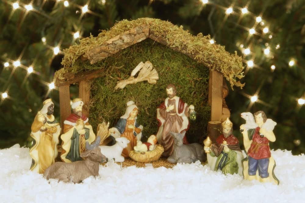 Rustic nativity set on white snow with twinkling lights in background