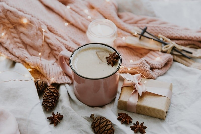 warm tones with mug of coffee, pincones and fairy lights