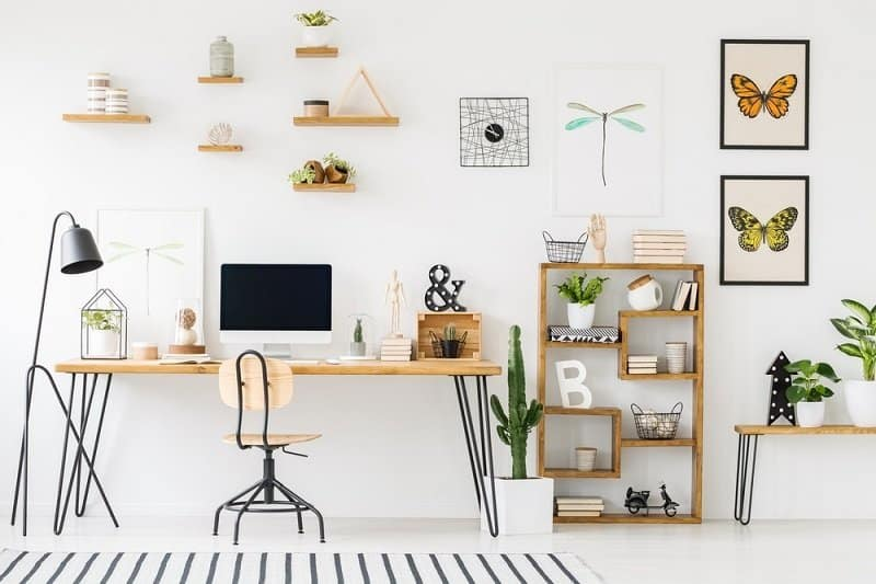 Home office with wood desk, minimal wood chair, shelves with plants, wall art
