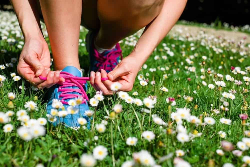 Woman tying her colorful running shoes in field of white flowers.