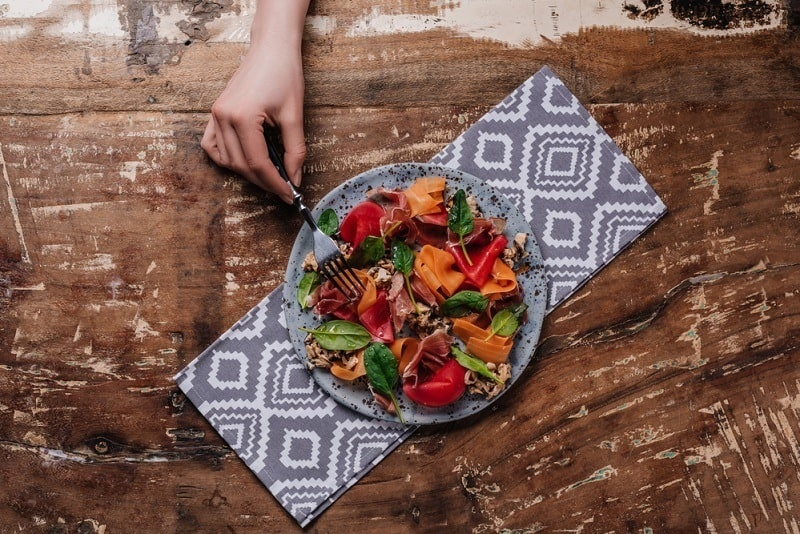 weight loss routine - colorful plate of salad on rustic wood table