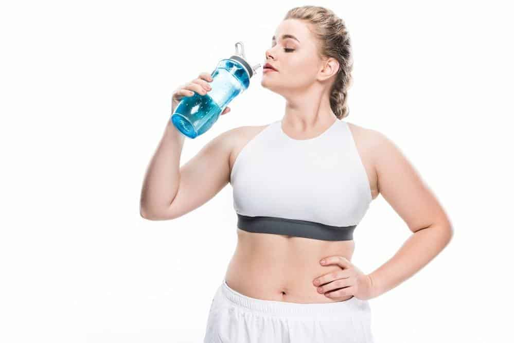 weight loss- woman in white workout clothes drinking from water bottle