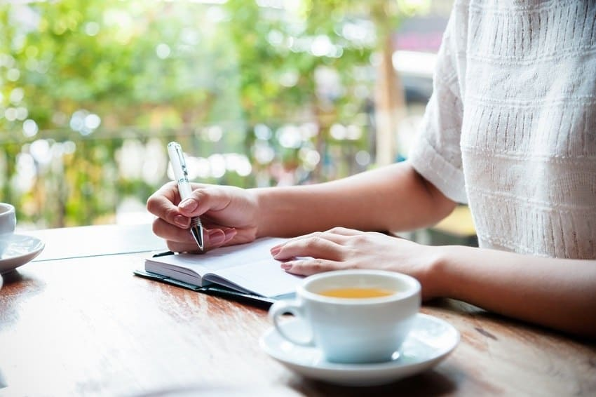 best morning routine -woman's hand writing in journal with cup of tea
