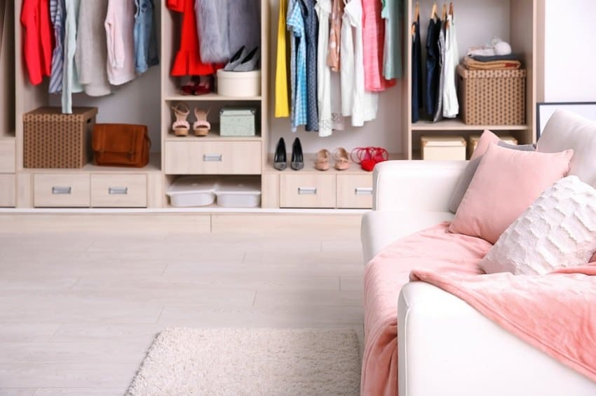 Woman's organized closet with white sofa and cozy pink throw blanket - declutter house in 30 days