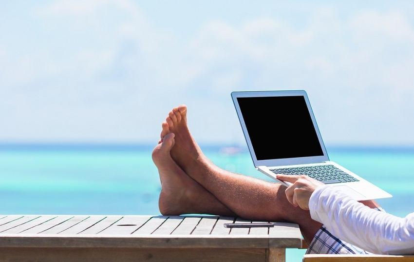 man with feet on table with open laptop and ocean in the background