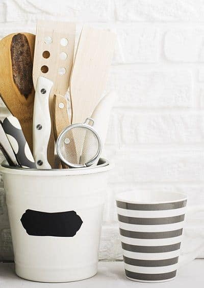 Kitchen utensils in white crock with plant and striped mug - declutter house in 30 days