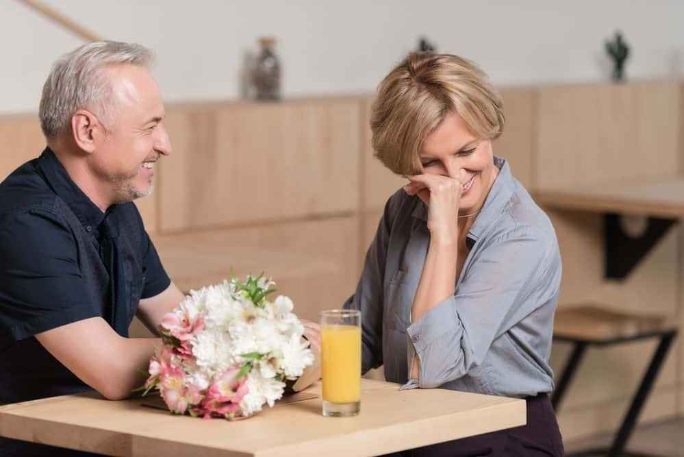 marriage advice - couple laughing at a table with flowers and orange juice