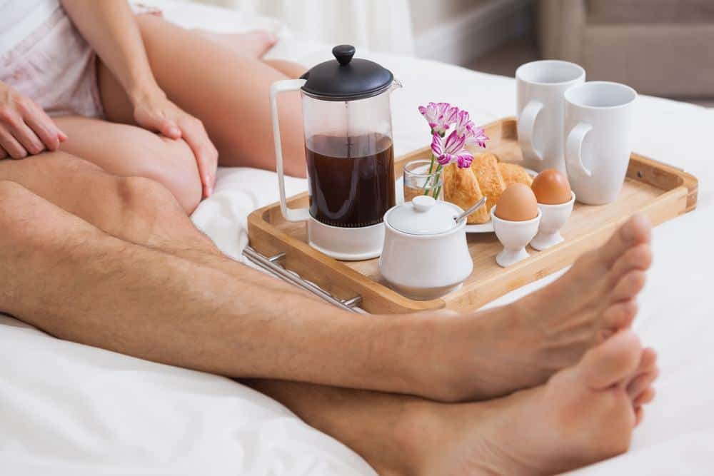 Leg shot of couple in bed enjoying coffee, eggs and pastry on a tray - marriage advice
