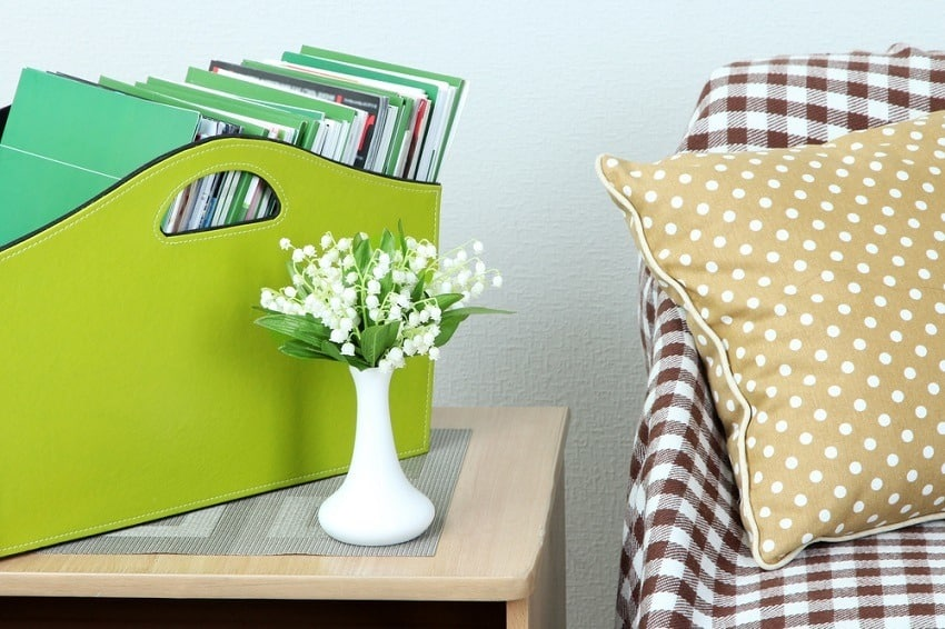 Plaid couch with side table and green basket of magazines - clearing clutter where to start.