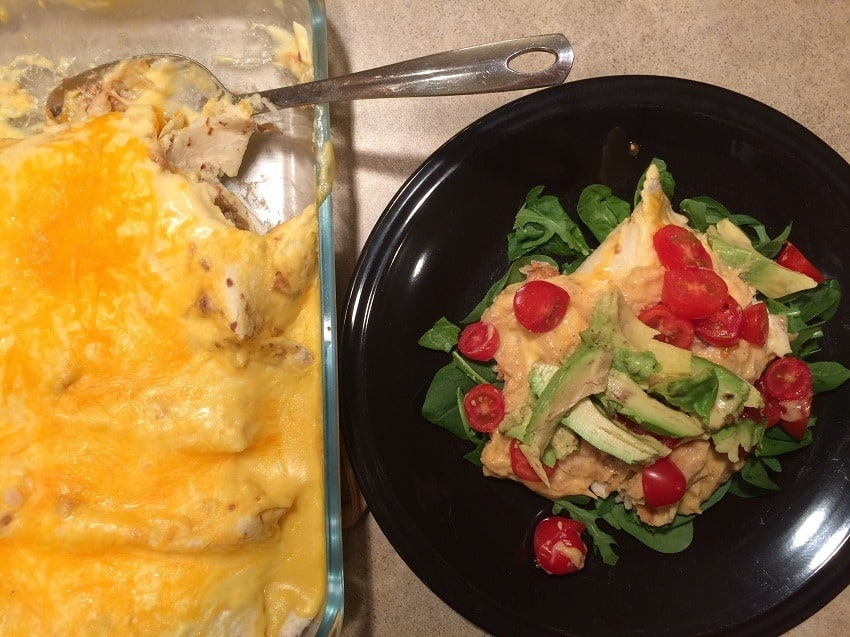 Easy leftover chicken recipes - chicken burritoes in casserole dish with serving of burrito on black plate