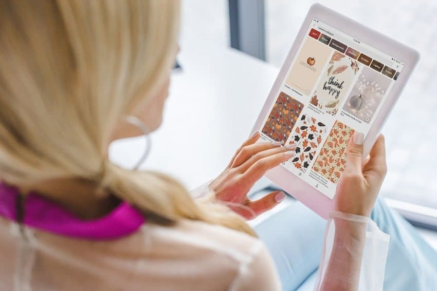 Blogging for money - blonde woman holding tablet with Pinterest on the screen