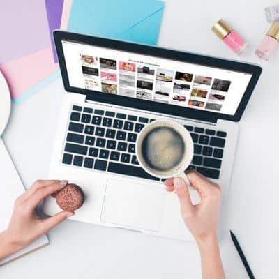 Blogging for money - woman with open laptop looking at pinterest holding coffee and cookie