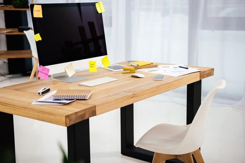 natural wood desk with computer and lots of sticky notes - blogging for money